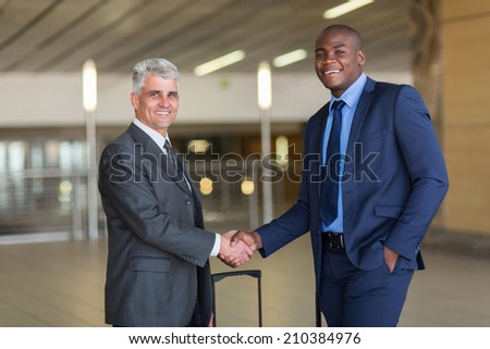 portrait of business travellers greeting at airport - stock photo