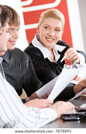 Portrait of business woman holding a pen and looking at her colleagues - stock photo