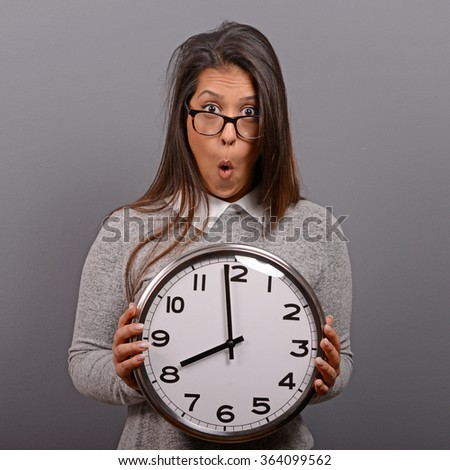 Portrait of business woman holding clock against gray background.Running late concept - stock photo