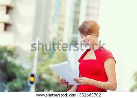 Portrait of business woman in red dress holding papers - stock photo