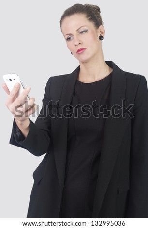 Portrait of business woman looking angrily in phone , isolated on white background - stock photo