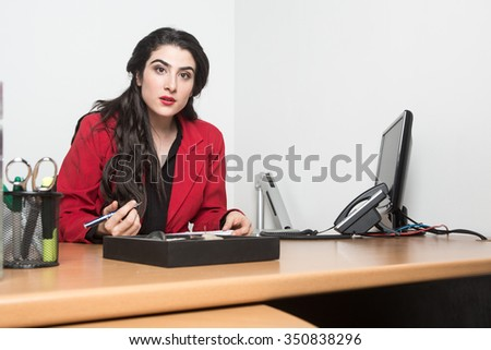 Portrait of business woman sitting in the office looking to the camera confident. She wears a red jacket and a black dress.