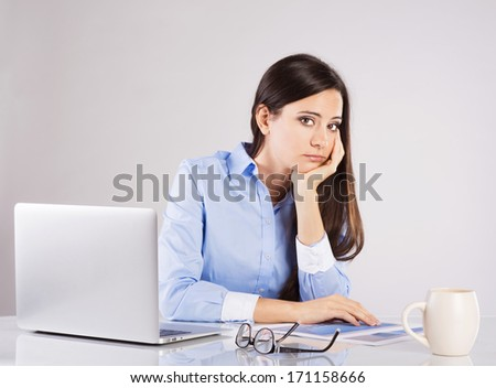 Portrait of Business woman sitting on her desk working with laptop isolated over gray background. - stock photo
