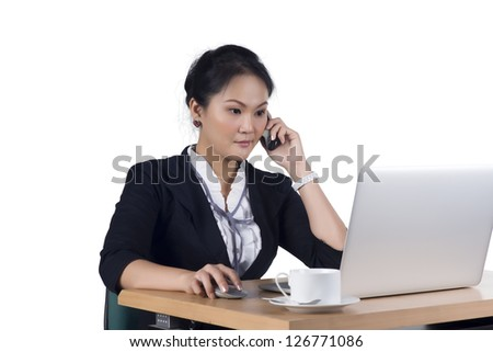 Portrait of business woman speaking on mobile phone while using laptop in office, Isolated white background. Model is Asian woman. - stock photo