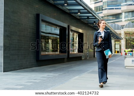Portrait of business woman walking and smiling outdoor - stock photo
