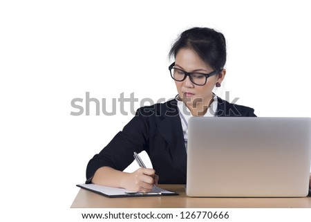 Portrait of business woman with laptop writes on a document at her office, Isolated on white background. Model is Asian woman.