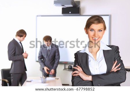 Portrait of business woman with team mates discussing in the background - stock photo