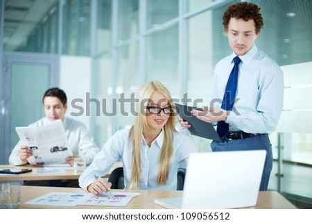 Portrait of business woman working on laptop with her colleague near by - stock photo