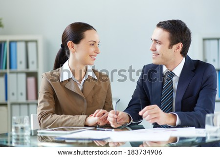 Portrait of businessman and businesswoman discussing plan or strategy at meeting - stock photo