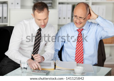 Portrait of businessman consulting his mad partner at desk in office - stock photo