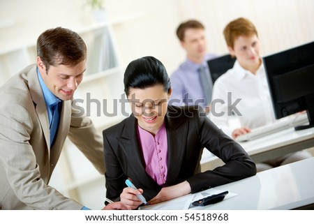 Portrait of businessman consulting pretty employee at meeting