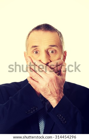 Portrait of businessman covering mouth.  - stock photo
