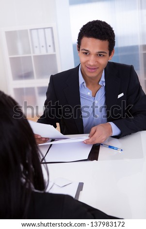 Portrait Of Businessman Discussing With His Co-worker In Office - stock photo