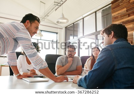Portrait of businessman explaining business plan to coworkers during a meeting in conference room.  Young people meeting in boardroom. - stock photo