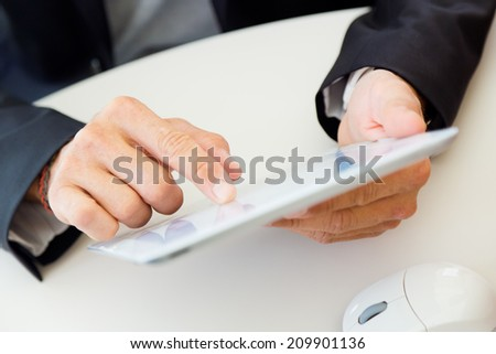 Portrait of businessman finger pointing to the screen of a digital tablet. - stock photo