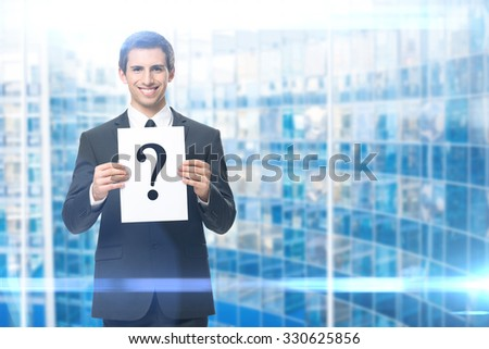 Portrait of businessman handing question mark, blue background. Concept of problem and solution - stock photo