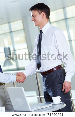 Portrait of businessman handshaking after signing contract - stock photo