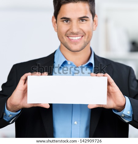 Portrait of businessman holding blank placard in office - stock photo