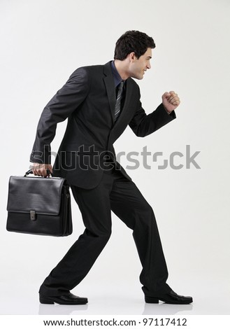 Portrait of businessman holding briefcase about to run
