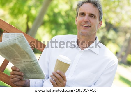Portrait of businessman holding newspaper and coffee cup in the park - stock photo