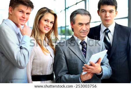 Portrait of businessman leading his team at office - stock photo