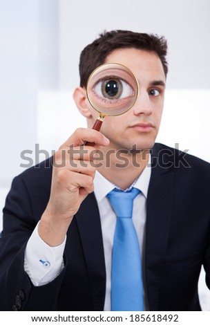 Portrait of businessman looking through magnifying glass in office - stock photo