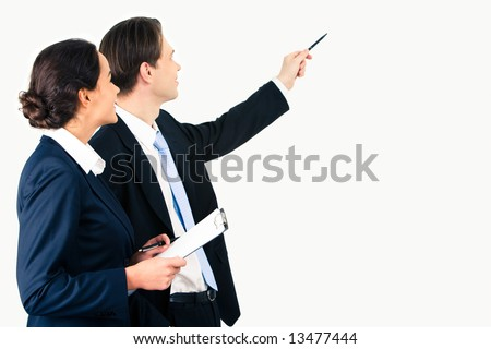 Portrait of businessman pointing at wall with woman near by - stock photo