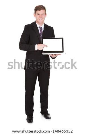 Portrait of businessman pointing on laptop isolated on white background - stock photo