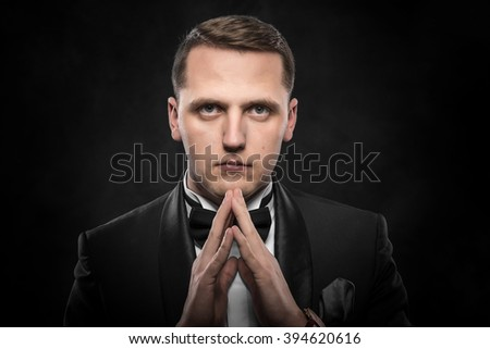 Portrait of businessman praying or thinking over dark background. - stock photo