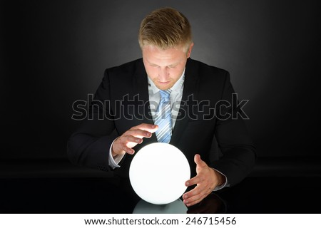 Portrait Of Businessman Predicting Future With Crystal Ball - stock photo
