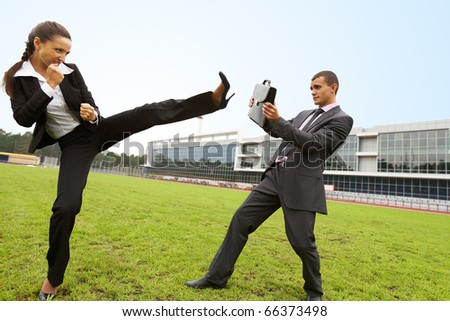 Portrait of businessman protecting himself with briefcase while aggressive businesswoman making kick by leg - stock photo