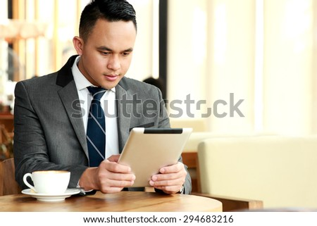 portrait of businessman reading an article on his tablets during coffee break with copyspace - stock photo