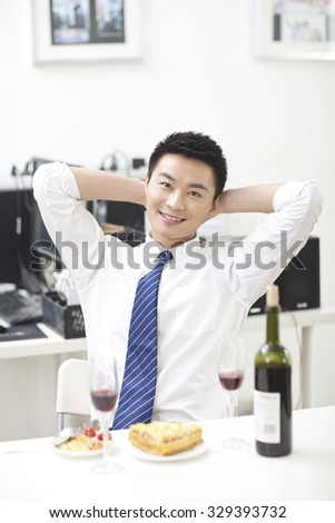 Portrait of businessman sitting at desk with food - stock photo