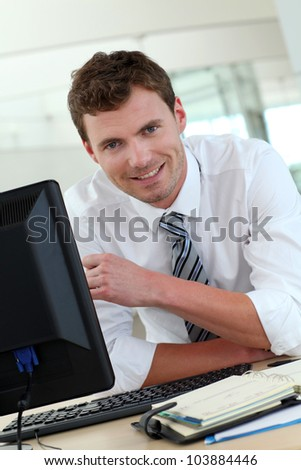 Portrait of businessman sitting at his desk in office - stock photo