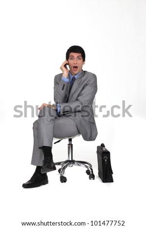 portrait of businessman sitting on swivel chair looking amazed - stock photo