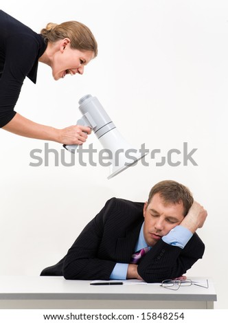 Portrait of businessman sleeping at workplace with businesswoman over him waking him up - stock photo