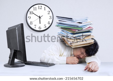 Portrait of businessman sleeping in office with documents  on his head after overtime - stock photo