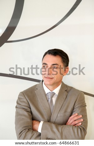 Portrait of businessman standing in hall - stock photo