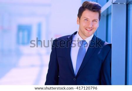 Portrait of businessman standing near window in office - stock photo
