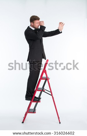 Portrait of businessman standing on the ladder and using telescope isolated on white. Man in suit dreaming to see the business future reality. - stock photo