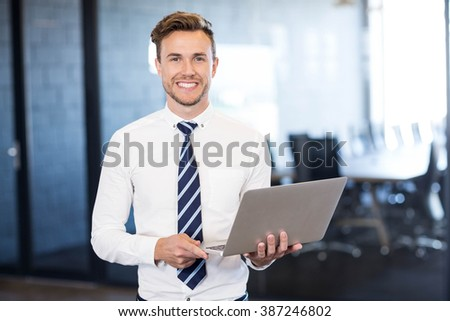 Portrait of businessman standing with a laptop in front conference room in office - stock photo