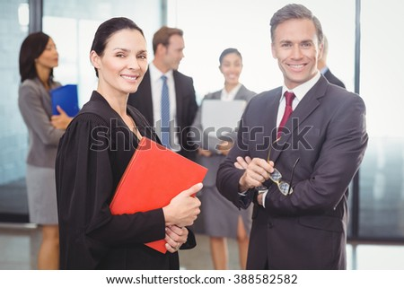 Portrait of businessman standing with lawyer in office - stock photo