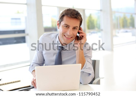 Portrait of businessman talking on mobile phone in office - stock photo