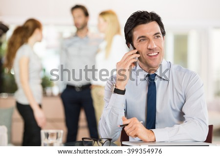 Portrait of businessman talking on telephone in office. Happy smiling business man sitting at meeting table talking on mobile phone. Portrait of business man talking on cellphone.