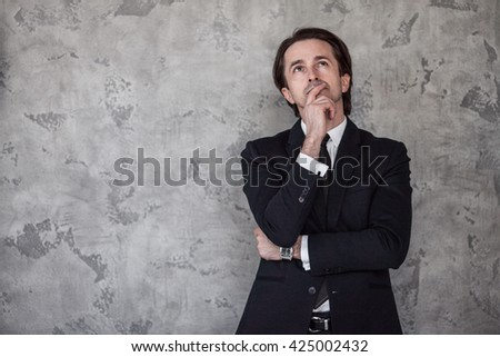 Portrait of businessman thinking against a concrete wall