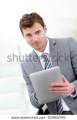 Portrait of businessman using electronic tablet in hall