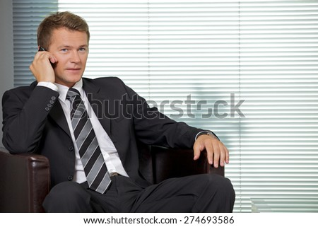 Portrait of businessman using mobile phone in office - stock photo