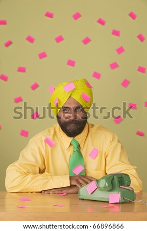 Portrait of businessman wearing turban with sticky notes attached everywhere - stock photo