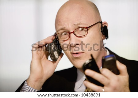 Portrait of businessman with several cell phones - stock photo