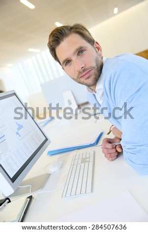 Portrait of businessman working on desktop computer